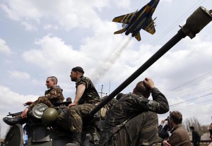 A fighter jet flies above Ukrainian soldiers in Kramatorsk