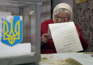 epa03450145 Elderly Ukrainian Katerina Sherdan reads her ballot papers before voting at her home during the Ukrainian parliamentary elections in the Krenichi village, about 40 kilometers from the capital Kiev, Ukraine, 28 October 2012. Voting began in Ukrainian parliamentary elections that opinion polls showed would deliver a reinvigorated opposition for the government as it faces charges of corruption and authoritarianism. Polling centres opened at 8 am (0600 GMT) and would close 12 hours later for the 36.6 million eligible voters to chose between the government side, led by President Viktor Yanukovych, and a united opposition, led by heavyweight boxing champion Vitali Klitschko and former prime minister Yulia Tymoshenko.  EPA/TATYANA ZENKOVICH